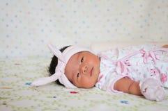 Konzentrieren Sie sich am Baby mit nettem Stirnband beim Dösen und Spielen mit netter Puppe auf das Bett Neugeborenes Mädchen ist Stockbild
