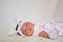 Konzentrieren Sie sich am Baby mit nettem Stirnband beim Dösen und Spielen mit netter Puppe auf das Bett Neugeborenes Mädchen ist Lizenzfreie Stockfotos
