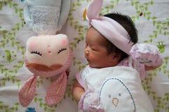 Konzentrieren Sie sich am Baby mit nettem Stirnband beim Dösen und Spielen mit netter Puppe auf das Bett Neugeborenes Mädchen ist Stockbilder