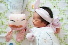 Konzentrieren Sie sich am Baby mit nettem Stirnband beim Dösen und Spielen mit netter Puppe auf das Bett Neugeborenes Mädchen ist Stockfotografie