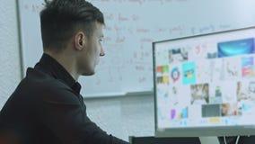 Konzentriert auf Arbeit Seitenansicht des überzeugten jungen Mannes, der zu Information über sein Notizbuch beim Sitzen an seinem stock footage