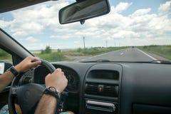 """Konzept †fahren """"Fahrerhände auf Rad- und Autoinnenraum stockbild"""