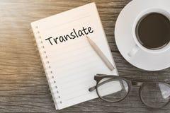 Konzept übersetzen auf Notizbuch mit Glas-, Bleistift- und Kaffeecu Lizenzfreie Stockfotos