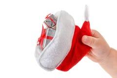 Konzept, children& x27; s-Hand hält einen Sankt-Hut und -geschenke Stockbilder