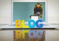 Konzept, das mit hölzernen Buchstaben auf einem Laptop auf einem hölzernen flo blogging ist Stockfoto