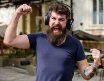 Konzept der drahtlosen Technologien Hippie mit Kopfhörern auf hörender Musik des glücklichen Gesichtes beim Gehen Mann mit langem Lizenzfreie Stockbilder