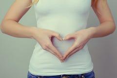 Konzept der ersten Wochenschwangerschaft Frau ` s Hände, die an Herz bilden lizenzfreies stockfoto