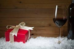 Konzept der Feier mit Geschenkbox, Weinglas auf Schnee Stockfoto