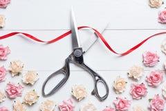 Konzept der festlichen Eröffnung mit den Scheren, die rotes Band auf Weiß schneiden Lizenzfreie Stockfotografie