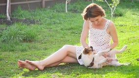 Konzept der Freundschaft und der Haustiere Gl?ckliche junge Frau und Hund, die Spa? am Gras hat stock video footage