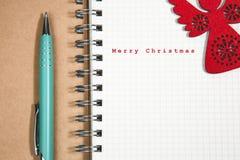 Konzept der frohen Weihnachten, Notizbuch und grüner Stift mit hölzernem Rot Lizenzfreie Stockfotografie