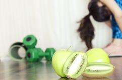 Konzept der gesunden Mahlzeit nach Übungen Flexible Frau, die Programm ausdehnend und frische Früchte nach Training bevorzugen tu stockfotos