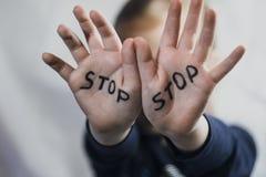 Konzept der häuslicher Gewalt und des Kind-abusement Ein kleines Mädchen zeigt ihre Hand mit dem Wort der HALT, der auf es geschr lizenzfreie stockfotos