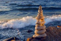 Konzept der Harmonie und der Balance Felsen-Zen bei Sonnenuntergang Balancen- und Gleichgewichtsteine gegen das Meer Stockfotografie