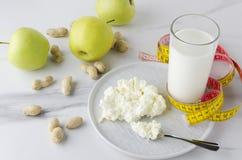 Konzept der köstlichen Mahlzeit für Milchdiät und Verlustgewicht Glas Milch, Platte mit Hüttenkäse, grüne Äpfel, Erdnüsse auf wei lizenzfreie stockfotos