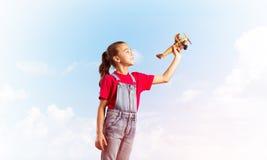 Konzept der unvorsichtigen glücklichen Kindheit mit dem Mädchen, das träumt, um Pilot zu werden Stockbild