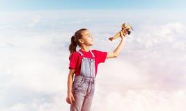 Konzept der unvorsichtigen glücklichen Kindheit mit dem Mädchen, das träumt, um Pilot zu werden Stockbilder