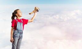 Konzept der unvorsichtigen glücklichen Kindheit mit dem Mädchen, das träumt, um Pilot zu werden Stockfotografie