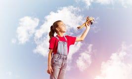Konzept der unvorsichtigen glücklichen Kindheit mit dem Mädchen, das träumt, um Pilot zu werden Lizenzfreie Stockfotos