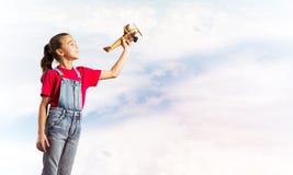 Konzept der unvorsichtigen glücklichen Kindheit mit dem Mädchen, das träumt, um Pilot zu werden Lizenzfreies Stockfoto
