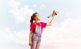Konzept der unvorsichtigen glücklichen Kindheit mit dem Mädchen, das träumt, um Pilot zu werden Stockfoto