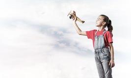 Konzept der unvorsichtigen glücklichen Kindheit mit dem Mädchen, das träumt, um zu werden Lizenzfreies Stockfoto