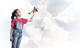 Konzept der unvorsichtigen glücklichen Kindheit mit dem Mädchen, das träumt, um zu werden Stockbild