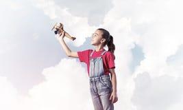 Konzept der unvorsichtigen glücklichen Kindheit mit dem Mädchen, das träumt, um zu werden Stockbilder