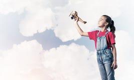 Konzept der unvorsichtigen glücklichen Kindheit mit dem Mädchen, das träumt, um zu werden Lizenzfreie Stockfotos