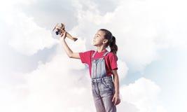 Konzept der unvorsichtigen glücklichen Kindheit mit dem Mädchen, das träumt, um zu werden Stockfoto