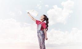 Konzept der unvorsichtigen glücklichen Kindheit mit dem Mädchen, das träumt, um zu werden Lizenzfreie Stockfotografie