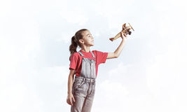 Konzept der unvorsichtigen glücklichen Kindheit mit dem Mädchen, das träumt, um zu werden Lizenzfreie Stockbilder