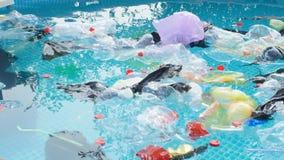Konzept der Verschmutzung des Planeten Plastiktaschen und Flaschen schwimmen auf das Wasser stock footage