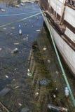 Konzept der Verschmutzung: Fischerboote auf dem schmutzigen Strand voll des Plastiks wirft weg Lizenzfreies Stockbild