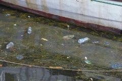 Konzept der Verschmutzung: Fischerboote auf dem schmutzigen Strand voll des Plastiks wirft weg Lizenzfreie Stockfotos