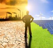 Konzept der Verschmutzung und der sauberen Energie. Geschäftsmann aufpassendes windmil