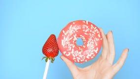 Konzept der Wahl zwischen Donut und Erdbeere weibliche H?nde mit rotem Nagellackgriff mit rosa Donut und Erdbeere an stockbild