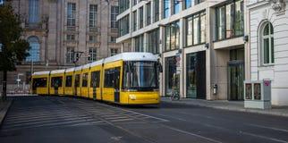 Konzept des öffentlichen Transports Gelbe elektrische Tramreisen an Berlins Stadt, Deutschland Gebäudehintergrund, Fahne lizenzfreie stockfotografie
