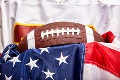 Konzept des amerikanischen Fußballs, Ball auf Hintergrund der amerikanischen Flagge und Uniform des amerikanischen Fußballs lizenzfreie stockfotografie
