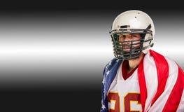 Konzept des amerikanischen Fußballs, Porträt des Spielers des amerikanischen Fußballs mit amerikanischer Flagge auf schwarzem Hin stockbild