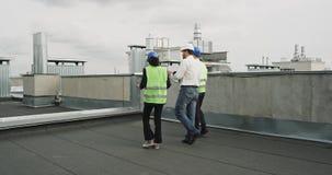 Konzept des Baubauleiters und -architekten, die den Plan der Baustelle auf der Dachspitze des Gebäudes analysieren stock video footage