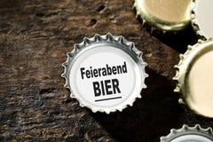 Konzept des Bieres nach der Arbeit mit Flaschenoberteilen Lizenzfreies Stockfoto