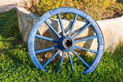 Konzept des Dekors für Garten - hölzernes Rad auf einem Hintergrund des grünen Grases Stockfotos