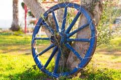 Konzept des Dekors für Garten - hölzernes Rad auf einem Hintergrund des grünen Grases Lizenzfreies Stockfoto