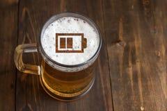 Konzept des Energiebieres Unterzeichnen Sie kleine Batterie auf dem Bierschaum im Glas Stockfotos