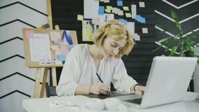 Konzept des Freiberuflich t?tig seins oder der B?roarbeit Junger weiblicher Grafikdesigner mit dem Arbeiten des kurzen Haares stock video