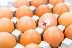 Konzept des gebrochenen Eies mit dem Verband gesetzt mit anderen Eiern auf tr Stockfotos