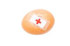 Konzept des gebrochenen Eies mit Verband mit anderen Eiern auf Behälter Stockbilder