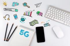 Konzept des Geschäfts 5G Schreibtischtabelle mit Computer, Smartphone, Notizblock, Bleistifte Stockbild