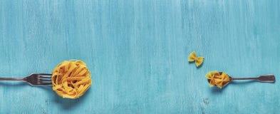 Konzept des Lebensmittels, Teigwaren auf einem blauen Hintergrund Stockbild